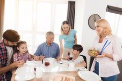 En stor familj samlade på matställetabellen En kvinna i blå disk för en T-tröjaraszlozhila, en annan kvinna kom med en sallad fotografering för bildbyråer
