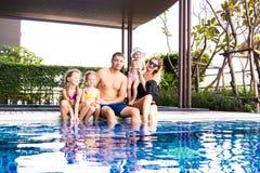 En stor familj sitter vid pölen i villan Mamma, farsa och tre döttrar Begreppet av en lycklig familj, ett stort arkivbild