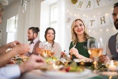 En stor familj som sitter på en tabell på ett inomhus födelsedagparti som äter arkivfoto
