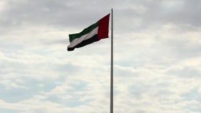 En stor flagga av UAE som högt flyger på staden av Sharjah, UAE En beröm för nationell dag på 2nd December stock video