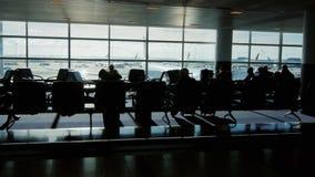 En stor flygplatsterminal på en solig dag Konturer av folk som väntar på ett flyg, flygplanet till och med fönstret lager videofilmer