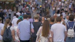 En stor folkmassa av folk som går ner gatan Ut ur fokus lager videofilmer