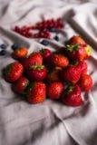 En stor gäst av saftiga röda jordgubbar ligger på draperat tyg blåbär röda vinbär i bakgrunden royaltyfria foton