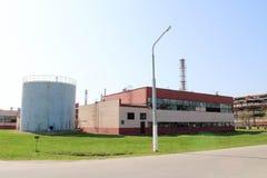 En stor grå färg belägger med metall behållaren, en trumma med en öppen lucka och en röd produktionbyggnad på ett oljeraffinaderi arkivfoton