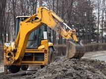 En stor gul grävskopa står i mitt av gatan nära det grävde hålet fotografering för bildbyråer