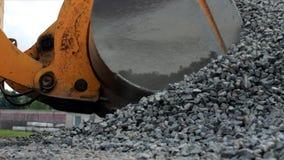 En stor gul laddare samlar den krossade stenen i en hink, en närbild, enmetall och en traktor lager videofilmer