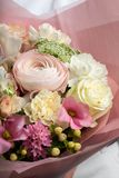 En stor härlig fördelande bukett av blommor i händerna av en flicka, arbetet av en blomsterhandlare royaltyfria foton