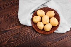 En stor hög av rå och unga potatisar i ett ljust tyg på trätabellen för mörk brunt Nya potatisar i en liten brun korg Royaltyfri Bild