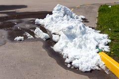 En stor hög av smutsig och vit snö ligger på asfaltvägen Royaltyfri Bild