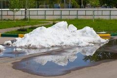 En stor hög av smutsig snö som ligger i pölen på asfaltroen Royaltyfri Foto