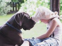 En stor hund och ett barn i en rolig hatt royaltyfri fotografi