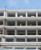 En stor konstruktionsplats av bostads- lägenheter med vita betongväggar och golv och arbetare i skyddskläder Royaltyfri Bild