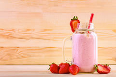 En stor krus med jordgubbesmoothien på ett stort ljus - brun trätabell Ett tunt och rakt rött sugrör i kruset med drycken Arkivbilder