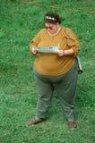En stor kvinna som läser en broschyr Royaltyfria Bilder