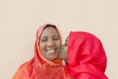En stor kyss på mammas kind Royaltyfri Bild