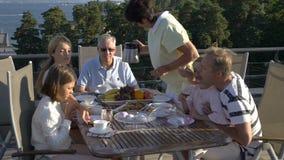 En stor lycklig familj har matställen på den öppna terrassen på taket av huset stock video