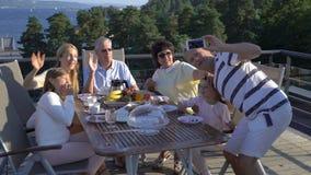 En stor lycklig familj tar ett familjfoto på en smartphone arkivfilmer