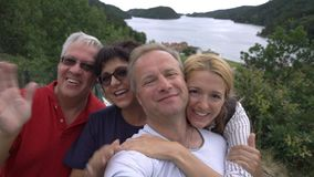 En stor lycklig familj tar en selfie eller en brukstelefon den videopd appellkameran på seacoasten arkivfilmer