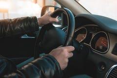 En stor man i ett läderomslag och jeans sitter bak hjulet av en bil arkivfoton