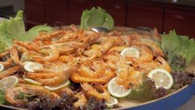 En stor maträtt mycket av lagade mat räkor med citron- och grönsallatsidor stock video