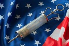 En stor medicinsk injektionsspruta ligger på amerikanska flaggan Royaltyfria Foton