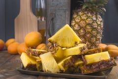 En stor och mogen ananas klipps in i stycken och en hel frukt Tropisk frukt på en träbakgrund och en ask med en snurrande för royaltyfri fotografi