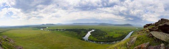 En stor panorama av en härlig grön äng med berg i bakgrunden och en flod längs dess hela längd Fotografering för Bildbyråer