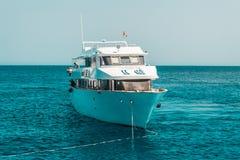 En stor privat motorisk yacht under vägen som seglar ut på det tropiska havet royaltyfria foton