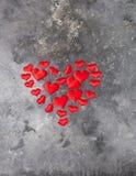 En stor röd hjärta fodras från små hjärtor på en grå texturerad bakgrund Begrepp av förälskelseferiehälsa Plan orientering arkivbilder