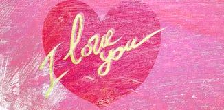 En stor röd hjärta i mitten med inskriften i guling älskar jag dig, mot målade oljor, rosa färger Royaltyfri Foto