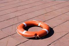 En stor rund orange plast- livcirkel för säkerhets- och räddningsaktionfolk i vattnet ligger på stengolvet arkivbild