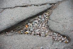 En stor spricka i asfalt som täckas med grus royaltyfria bilder