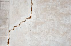 En stor spricka på den gråa väggen abstrakt bild som projekterar en spricka i en vit betongvägg royaltyfri foto