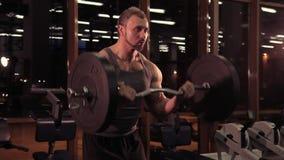 En stor stark man pumpar hans muskler med en skivstång lager videofilmer