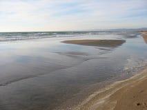 En stor strand av sand i vinter med havet som kommer nära italy Arkivfoton