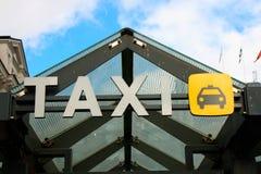 En stor taxi undertecknar in staden arkivbilder