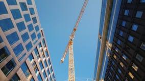 En stor tornkran i centret av den moderna staden Glass kontorsbyggnader omkring Sned bollskott för låg vinkel fotografering för bildbyråer