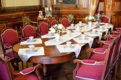 En stor träbrun gammal antik tabell för berömmar, festmåltider, banketter, möten, förhandlingar med porslinet och röda mjuka stol arkivfoto