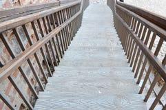 En stor träbrun trappuppgång som ner leder med moment och räcke grönska för abstraktionbakgrundsgentile royaltyfri bild