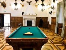 En stor trämassiv dyr billiardtabell för att spela biljard i ett rum med en spis och att jaga troféer royaltyfria foton