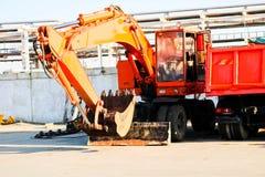 En stor tung gul orange lastbil med en släp, en dumper och en grävskopa med en slev parkeras i rad på en konstruktion fotografering för bildbyråer