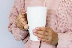 En stor vit kopp f?r kaffe eller te i h?nderna av en ikl?dd ung kvinna en stucken kofta av persikaf?rg arkivfoton