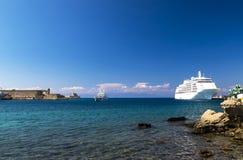 En stor vit kryssningeyeliner står på en skeppsdocka i en pittoresk turist- port på den grekiska ön av Rhodes royaltyfri bild