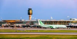 En storartad aftonhimmel över en modern flygplats som glöder med la Arkivfoton