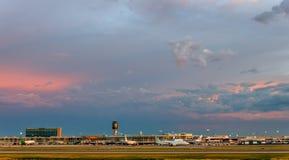 En storartad molnig aftonhimmel över en modern flygplats som glöder Royaltyfria Foton