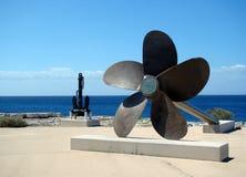 En stort propeller och ankare som lokaliseras på kusten Arkivbild