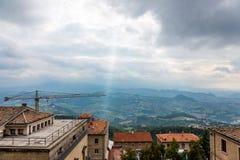 En stråle av solavbrott till och med de mörka molnen mot bakgrunden av bergen i San Marino fotografering för bildbyråer