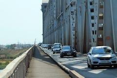 En ström av bilar på den gammala bron i Astrakhan Royaltyfri Foto