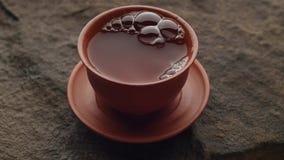 En ström av nytt varmt grönt te som flödar in i en keramisk bunke på en grov naturlig sten arkivfilmer
