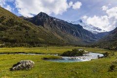 En ström och en snö caped berg i den Huascaran nationalparken Fotografering för Bildbyråer
